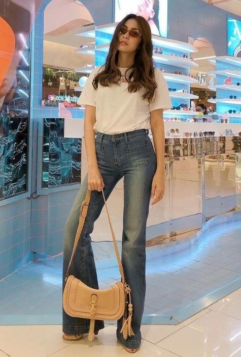 Hà Tăng diện streetstyle đơn giản với áo thun trắng, jeans và túi theo phong cách Boho phóng khoáng. Tuy nhiên, để xử lí chiếc quần quá dài này, người đẹp phải cố gắng tạo dáng chân nên trông rất gượng gạo.