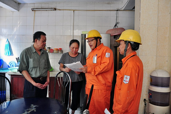 Ông Lê Văn Kỳ - Tổ trưởng tổ dân phố 13 phường Trung Tự phối hợp cùng công nhân Điện lực Đống Đa tuyên truyền đảm bảo an toàn điện trong mùa mưa bão