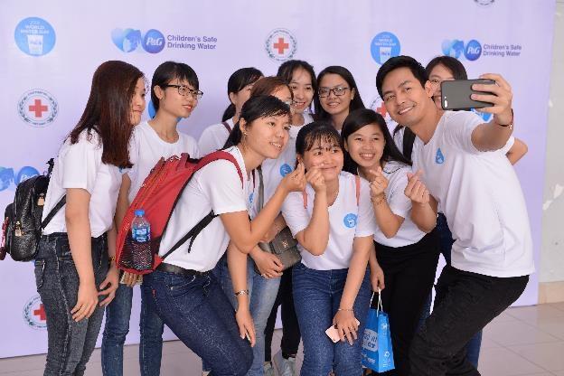 MC Phan Anh có mặt từ sớm và vui vẻ chụp hình kỷ niệm với các bạn sinh viên trường Đại Học An Giang, những tình nguyện viên của chương trình Nước Uống Sạch Cho Trẻ Em, giúp mang nước sạch về với các gia đình ở vùng khó khăn.