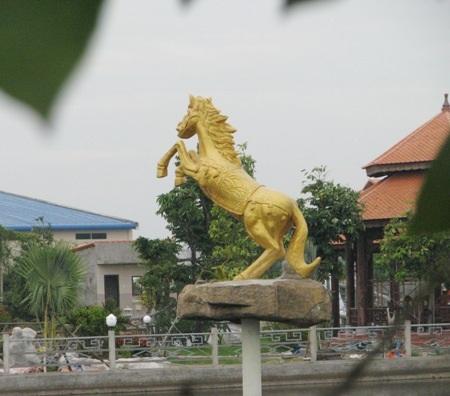 Có một hồ nước rộng lớn, với bức tượng ngựa màu vàng nổi bật giữa hồ.