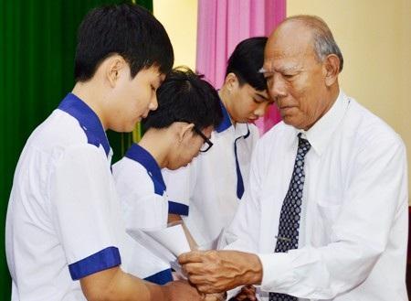 Thầy Lâm Es đang trao học bổng cho học sinh.