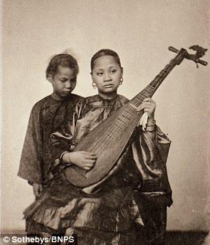 Người phụ nữ đang chơi món nhạc cụ truyền thống.