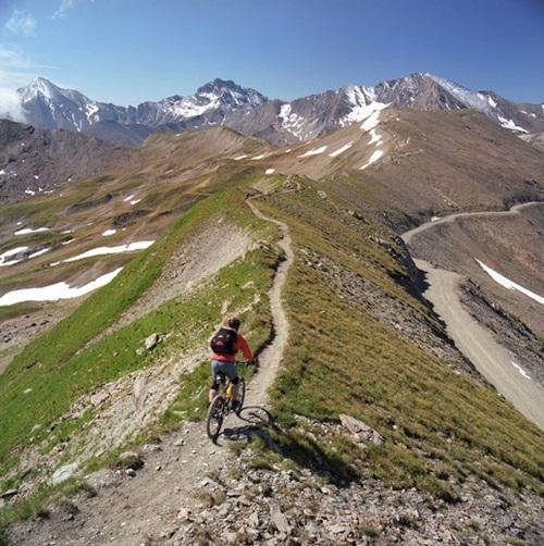 Một vận động viên xe đạp đi qua ranh giới giữa hai quốc gia Thụy Sỹ (bên trái) và Áo (bên phải). Đường biên giới ở đây là lối đi nhỏ.