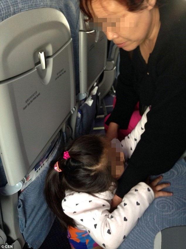 Một nữ du khách lớn tuổi cho cháu gái đi WC ngay trên sàn máy bay