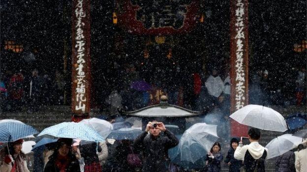 Du khách chụp hình tuyết rơi tại chùa Senso-ji – một trong những ngôi chùa cổ nhất và quan trọng bậc nhất tại thủ độ Tokyo