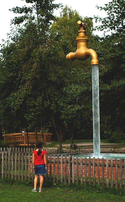 Một bé gái đang say mê ngắm nhìn dòng nước chảy từ trên cao xuống từ vòi phun ở Thụy Sỹ.