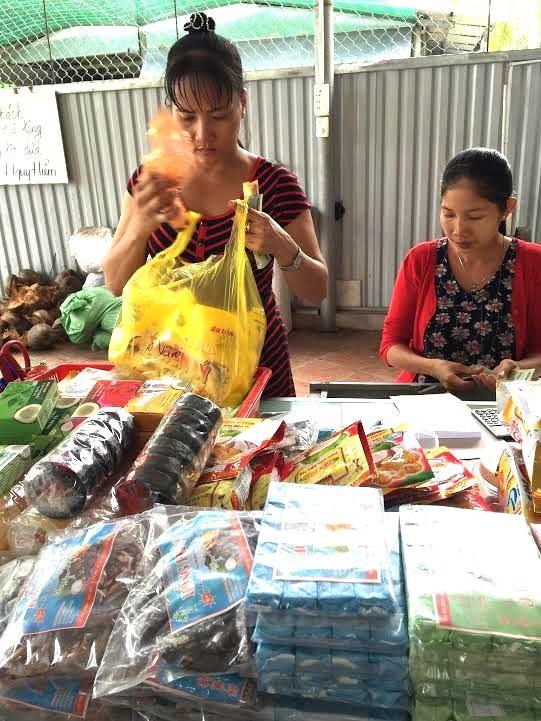Người bán hàng thoăn thoắt gói đồ cho khách trong một cơ sở sản xuất kẹo dừa ở ấp Thới Sơn, thành phố Mỹ Tho, Tiền Giang