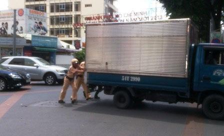 CSGT đội Bàn Cờ, TPHCM xuống đường giúp dân đẩy xe để giải tỏa ùn tắc (ảnh: Công Quang)