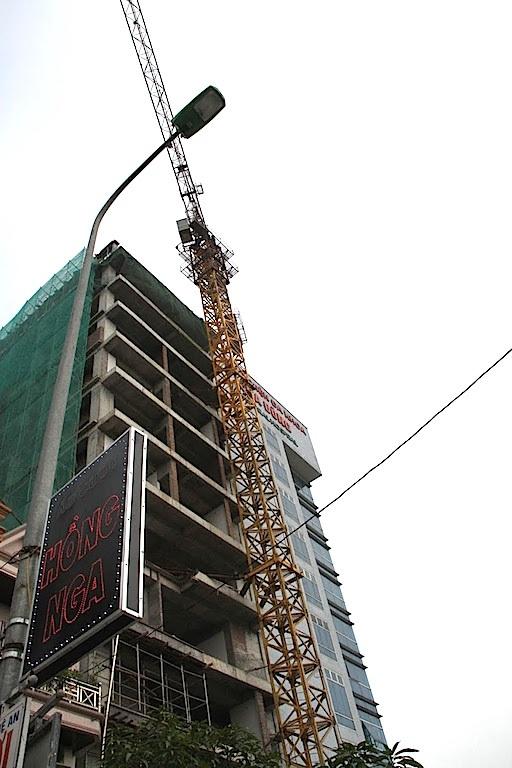 Một chiếc cần cẩu cao hàng chục mét của một toàn nhà đang thi công.