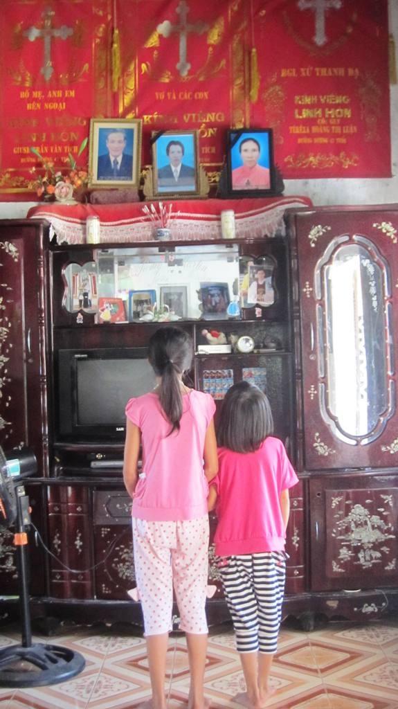 Nỗi nhớ thương của những đứa bé thơ dại trong căn nhà vắng bóng bố mẹ. Hai em Hường và Hồng ngước nhìn di ảnh bố mẹ