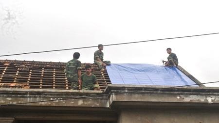 Các chiến sĩ bộ đội đơn vị 968, Quân khu 4 đang giúp dân sửa nhà, dọn vệ sinh