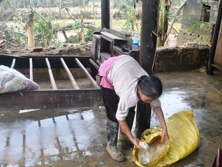 Bà Liến đau đớn nhìn số lúa, gạo bị ướt sũng trong nước