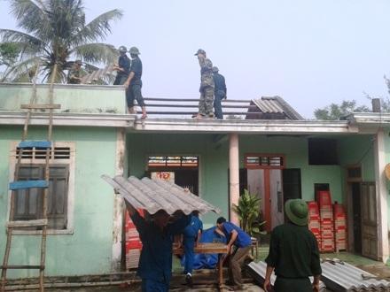 Các cán bộ, chiến sĩ Đồn Biên phòng 200 giúp người dân khắc phục hậu quả của bão