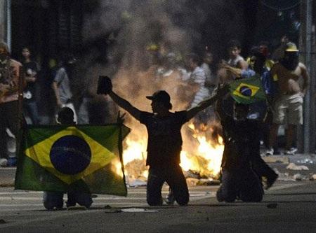 Những người biểu tình mang quốc kỳ Brazil quỳ trước một đám cháy được đốt lên trên đường