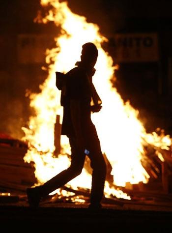 Hình ảnh một người biểu tình đi qua đám cháy lớn