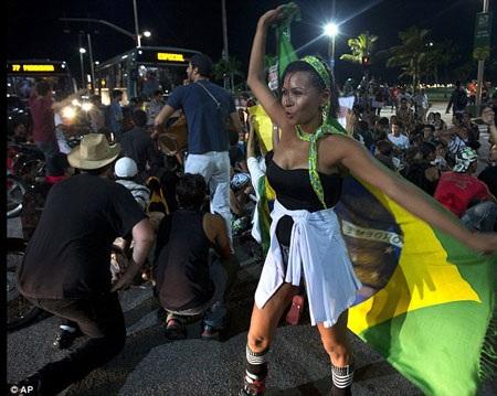 Một vũ công mang quốc kỳ brazil múa cổ vũ trong đoàn người biểu tình