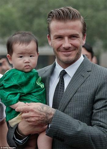 Beckham tươi cười vui vẻ khi bế em bé