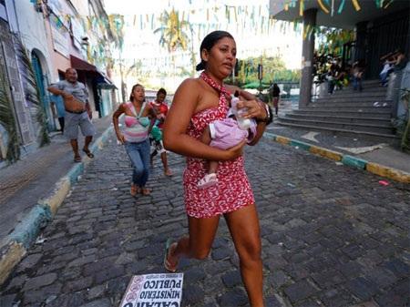 Một phụ nữ sợ hãi bồng con chạy nhanh qua khu vực xảy ra biểu tình