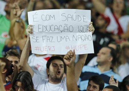 """Tấm biểu ngữ với dòng chữ """"Y tế và giáo dục làm nên một đất nước"""" được một CĐV giơ cao tại Maracana"""