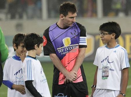 Messi trông khá bẽn lẽn bên cạnh các em nhỏ