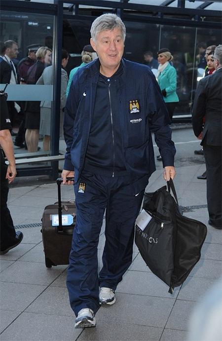 Trợ lý Brian Kidds lỉnh kỉnh đồ đạc rời sân bay