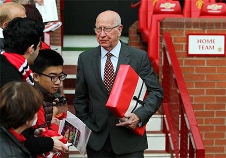 Huyền thoại Bobby Charlton cầm hộp quà trên tay....