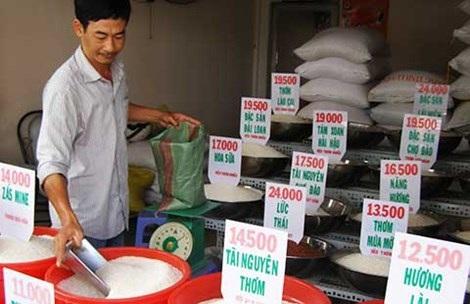 Ông Quang đang bán gạo cho khách hàng. Ảnh: T.NGỌC