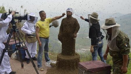 Những người hỗ trợ đốt hương và thuốc lá để không cho ong bám vào mặt