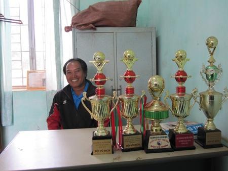 Huấn luyện viên Khiêm bên những chiếc cúp và huy chương mà ông và các cầu thủ nghèo đạt được