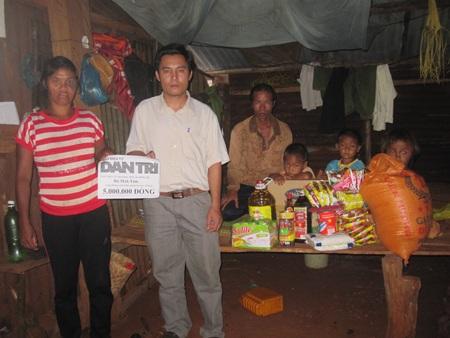 Đại diện chính quyền địa phương thay mặt bạn đọc trao quà cho gia đình chị Tăm