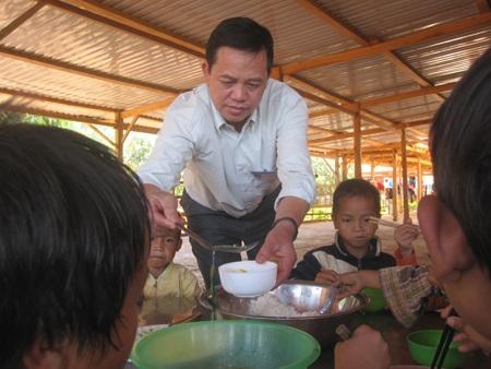 Thầy Tuấn lấy cơm cho học sinh nhỏ nhất trường