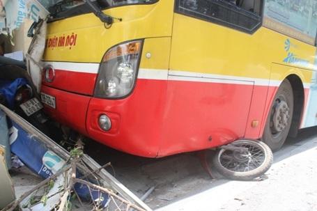 1 chiếc xe máy vẫn còn bị mắc kẹt dưới gầm xe buýt