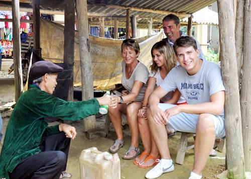 Những người khách nước ngoài thích thú thưởng thức rượu ngô ở chợ phiên Lùng Khấu Nhin.
