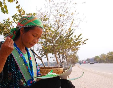 Người phụ nữ dân tộc thảnh thơi ngồi thêu trên đường phố