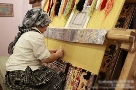 Một người thợ tỷ mỷ dệt thảm bằng tay
