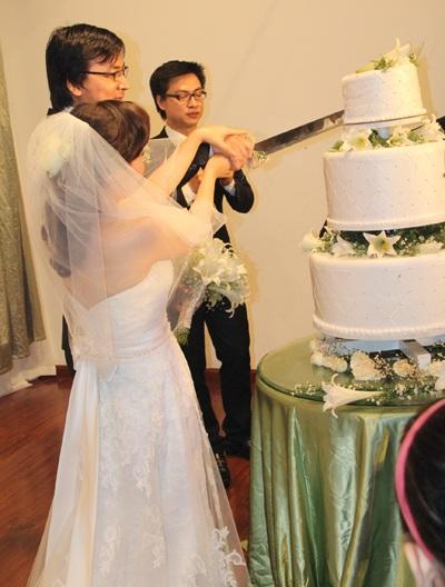 Cô dâu chú rể cắt bánh cưới.