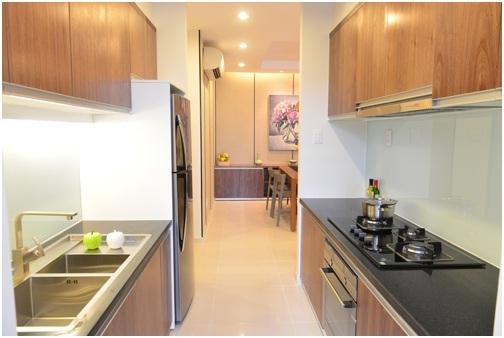 Căn hộ gồm phòng bếp, phòng ăn, phòng khách được nối với nhau, hài hòa trong ánh sáng ấm áp