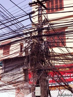 Một cột điện chằng chịt dây cáp viễn thông như mạng nhện ở Việt Nam đăng tải trên Economist.
