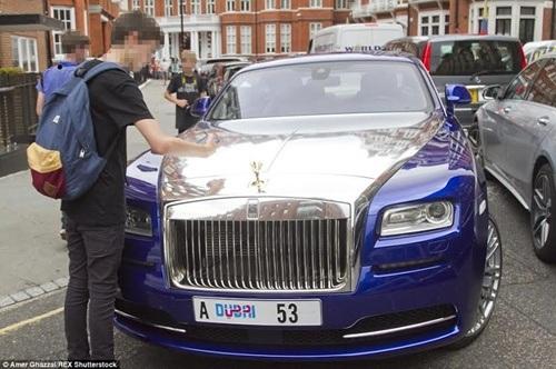 Nhiều người đi đường dừng lại chụp hình siêu xe Rolls Royce mang biển số đến từ Dubai.
