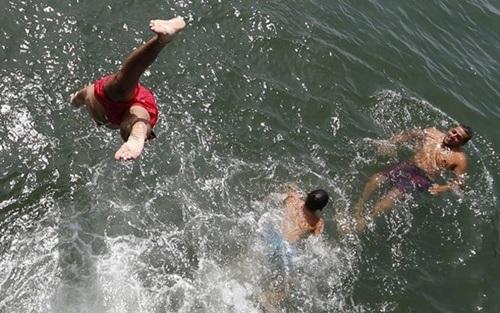 Các thanh niên thích thú ngâm mình trong dòng nước mát ở Arcachon thuộc miền Tây Nam Pháp.