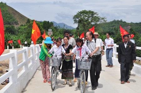 Các em học sinh cùng đại biểu đi trên cây cầu mới hoàn thành
