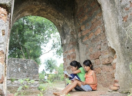 Góc học tâm của 2 cháu Dung và Hạnh dưới cổng vòm vào đền.