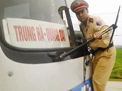 Một chiến sĩ CSGT đu bám vào cần gạt nước xe khách để tránh cú đâm trực diện.