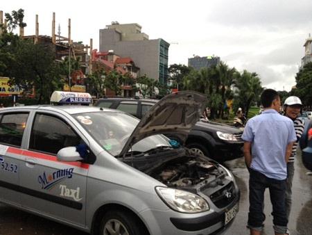 Một ô tô nằm chết giữa đường, nhiều xe khác nằm chờ cứu hộ (Ảnh: Bảo Trung)
