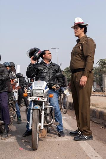 """Một người đàn ông đi xe motor dừng lại trên phố để chụp hình chung với cảnh sát Rajesh Kumar, 38 tuổi, có chiều cao 2,13m, người được cho là """"cảnh sát cao nhất Ấn Độ"""" hiện nay. (Ảnh: Asia Press)"""