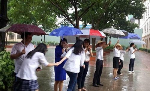 Thầy cô xếp thành hàng dài cầm ô che cho học sinh khỏi ướt