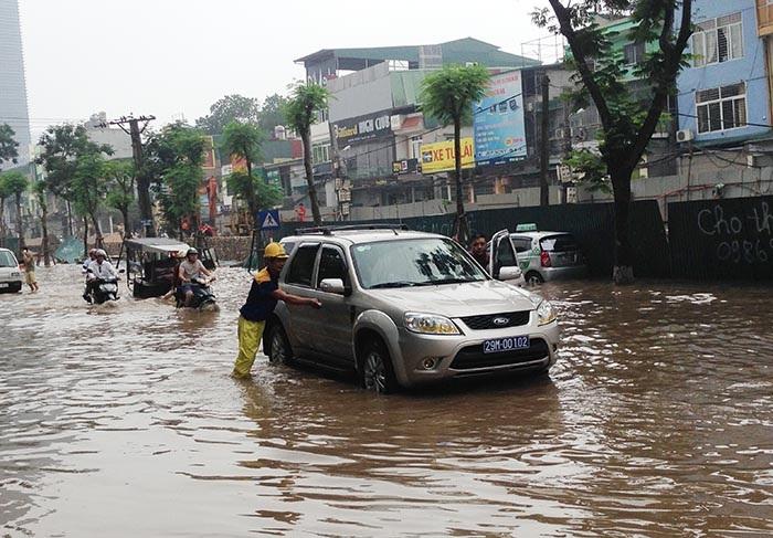 Lao vào vùng ngập nước lớn trên phố Thái Hà, chiếc xe này đã bị chết máy và phải nhờ người đẩy ra khỏi chỗ ngập. Ảnh: Việt Hưng