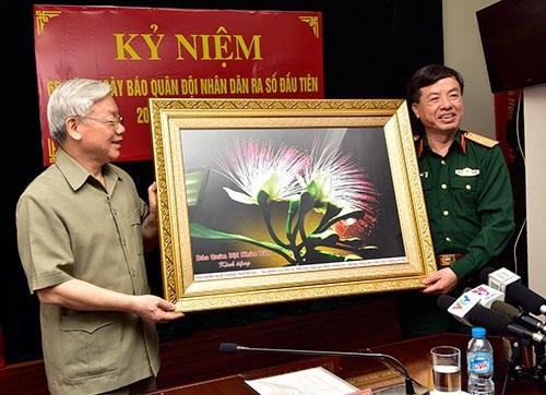 Thiếu tướng Phạm Văn Huấn, thay mặt tập thể Báo QĐND, tặng Tổng Bí thư Nguyễn Phú Trọng bức ảnh hoa bàng quả vuông, do phóng viên Báo QĐND chụp tại quần đảo Trường Sa.