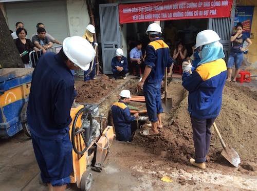 Nhiều công nhân cùng phương tiện máy móc đang đào xới trước cổng nhà 146 Quán Thánh trong khi người dân căng băng rôn kiên quyết phản đối.