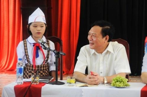 Bộ trưởng Phạm Vũ Luận đang nghe một em học sinh trường tiểu học Thụy Phong kể lại câu truyện Sơn Tinh - Thủy Tinh đã đọc được ở tủ sách phụ huynh.